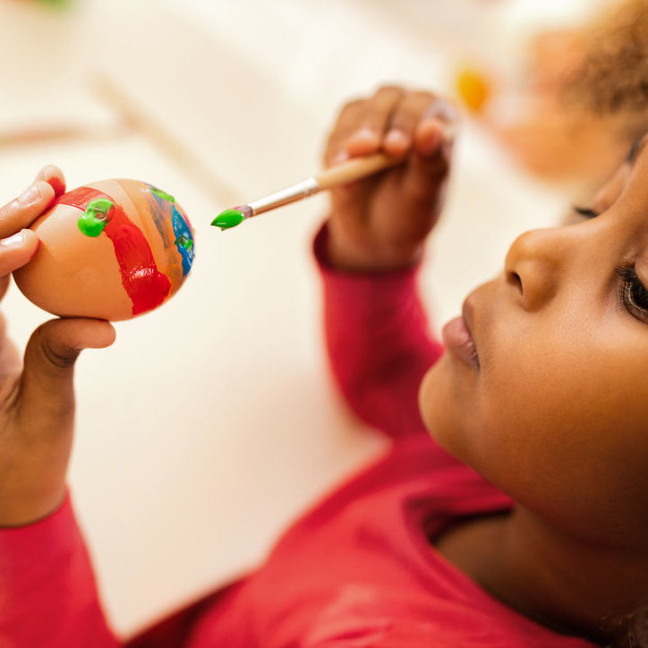 Close up of African American little girl coloring Easter egg with paintbrush.